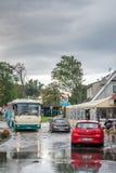 Buss och bilar på en översvämmad gata royaltyfri bild