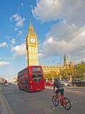 Buss och cykel bredvid parlamentet, London Arkivbild