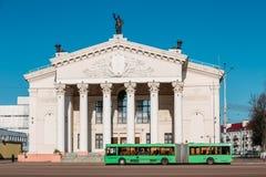 Buss som fortskrider gatan nära byggnad av Gomel den regionala dramateatern Arkivfoto