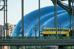 Buss som in korsar Tyne Bridge och Sage Gateshead Concert Hall arkivbilder