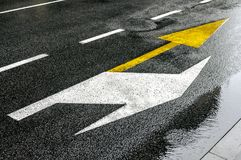 Buss yellow arrow showing straightforward and white right signs. In the city asphalt Stock Images