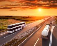 Bussa och åka lastbil i rörelsesuddighet på huvudvägen Royaltyfri Foto