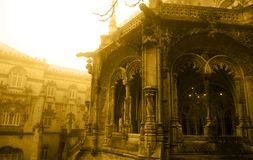 Bussaco Palace, Gothic Gargoyles, Tracery Arched Enclosed Balcony, Foggy Day, Sepia Image. Neo-Manueline style front arched enclosed balcony with spouts carved Royalty Free Stock Photo