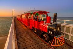 Busselton Train sunset. Busselton, Australia - Dec 30, 2017: Busselton Jetty Train on the longest wooden pier tracks in the world stretching almost 2 km out to Royalty Free Stock Image