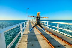 Busselton Jetty enjoying. Carefree young sporty woman jumping at Busselton jetty in Busselton, Western Australia. Happy female jumper over iconic wooden pier in royalty free stock photos