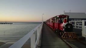 Busselton Train with moon. Busselton, Australia - Dec 30, 2017: running Busselton Jetty Train on tracks of railway over longest wooden pier in the world stock video