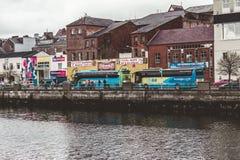 Bussen op de Kadestraat van Heilige Patrick ` s dichtbij de rivier Lee in Cork worden geparkeerd, Ierland dat stock afbeeldingen