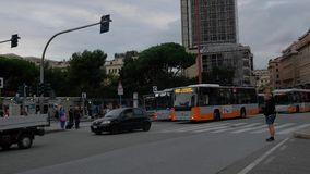 Busses and people passing by in front of the main train station of Genoa stock video footage