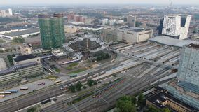 Busses and trains arriving at large scale train station Utrecht central with office buildings and transit oriented development. Busses and trains arriving at stock footage