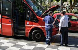 Bussförare och mekaniker som argumenterar, medan bussens hätta är öppen royaltyfri foto