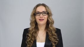 Bussines female stands worrying in expectation and then smiles with relief at grey background. Bussines female in glasses stands worrying in expectation and then stock video footage