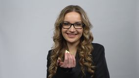 Bussines woman coquettishly smiling and showing gesture come here. Grey background at studio. Girl with wavy hair and glasses wearing a black business suit stock footage