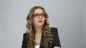 Bussines woman in glasses stands in expectation at grey background. Bussines woman in glasses stands in expectation against grey background at studio. Girl with stock footage