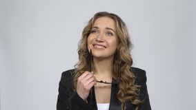 Bussines woman looks at the camera with a smile, takes off her glasses and a dream about something against grey. Background at studio. Girl with wavy hair and stock video footage