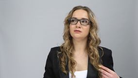 Bussines woman stands worrying in expectation at grey background. Bussines woman in glasses stands worrying in expectation against grey background at studio stock footage