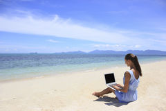 Bussines woman working on the beach with a laptop Royalty Free Stock Photography