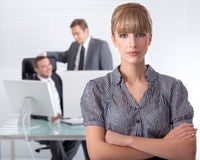 Bussines woman wth her associates. Businesswoman in his clean high tech office with associates in the background laughing Royalty Free Stock Image