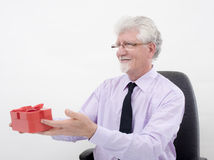 Bussinesman and gift. Senior businessman holding  a gift over white Royalty Free Stock Photography