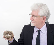 Bussinesman holding a nest with eggs. Senior businessman holding nest with eggs Stock Photos