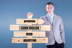 Bussinesman holding a wooden sign learn English Stock Image