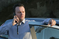 Bussinesman talk. Businessman talking over cellphone outside of his car because he have sence for security on road (never talk on your cellphone during the drive Stock Photo