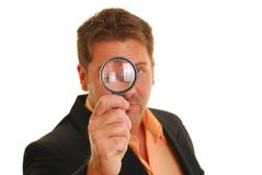Bussiness man holding a magnifying glass Royalty Free Stock Image