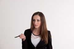 Business Woman Is Explaining Something with Pen  on Whi. Young Business Woman with Long Brown Hair is Explaining Something with Pen  on White Background Royalty Free Stock Images