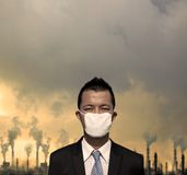 bussinessman con la máscara y la contaminación atmosférica Foto de archivo libre de regalías