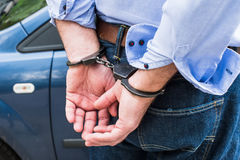Bussinessman in handcuffs. The man, a businessman in handcuffs. The arrest of the car Stock Image