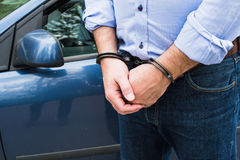 Bussinessman in handcuffs. The man, a businessman in handcuffs. The arrest of the car Royalty Free Stock Image