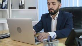 Bussinessman joven acertado que trabaja en el ordenador portátil almacen de video