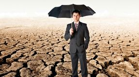 Bussinessman with umbrella in a desert Royalty Free Stock Photography