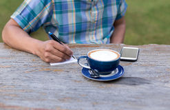 Bussinessman writting something on paper with  coffee cup and ce Royalty Free Stock Photography