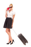 Bussineswoman con el pasaporte que espera con la maleta. Fotografía de archivo