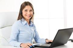 Bussineswoman con un auricular, mecanografiando en el ordenador portátil Imagen de archivo