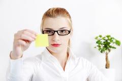Bussineswoman, das gelbes Blatt Papier betrachtet. Stockbilder