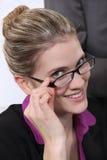 Bussineswoman rubio alegre tocando sus vidrios Fotografía de archivo libre de regalías
