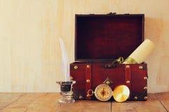 Bussola antica, inlwell e vecchio petto di legno sulla tavola di legno Immagine Stock