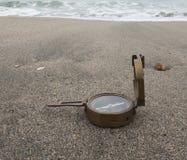 Bussola bronzea dell'annata sui precedenti del mare sulla sabbia Immagini Stock