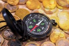 bussola con la moneta di oro Fine in su fotografie stock libere da diritti