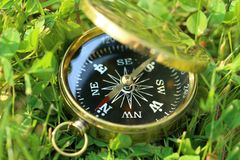 Bussola dorata su erba Fotografia Stock