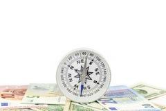 Bussola sulla banconota per la direzione finanziaria su fondo bianco Fotografia Stock