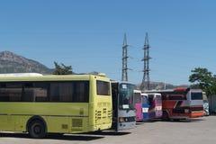 Bussstation med färgrika bussar Två elektriska stolpar på bakgrunden Fotografering för Bildbyråer