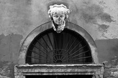 Bust. Above a worn doorway in Venice Stock Photos