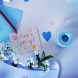 Busta bianca con i fiori della ciliegia, la matita, la carta colorata e la cartolina d'auguri con la molla Fotografia Stock Libera da Diritti
