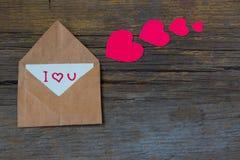 Busta con la carta ed il testo ti amo e cuori rossi per valent Immagini Stock