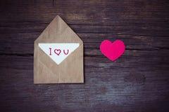 Busta con la carta ed il testo ti amo e cuori rossi per valent Fotografia Stock