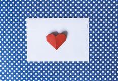 Busta del Libro Bianco e cuore di origami su un fondo blu polk Immagine Stock