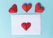 Busta del Libro Bianco e cuori rossi di origami su un fondo blu Fotografia Stock