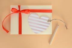 Busta giallo-chiaro con un nastro, una carta del cuore e una matita rossi su un fondo dell'albicocca Fotografie Stock